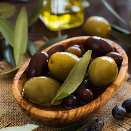 Olive oil and olives on rustic wood background