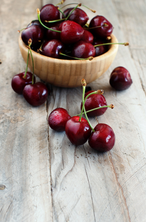 Red cherries in a bowl on a old wooden background Archivio Fotografico