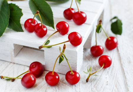 Fresh sour cherries  on a white wooden table