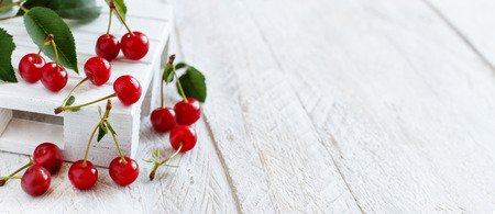 Fresh sour cherries with leaves on a white wooden table