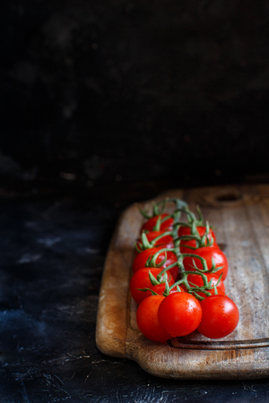 Cherry tomatoes on a dark background close up Archivio Fotografico