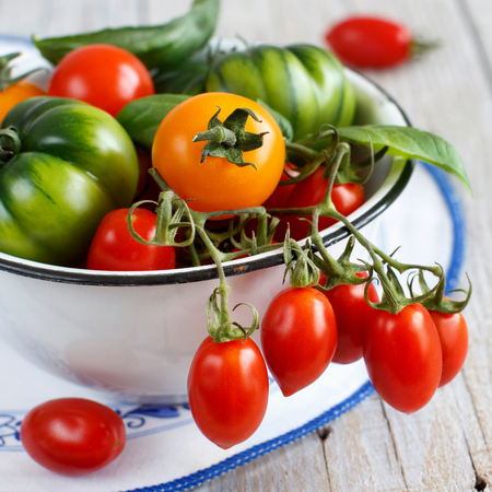 Colorful tomatoes in a bowl on a wooden table