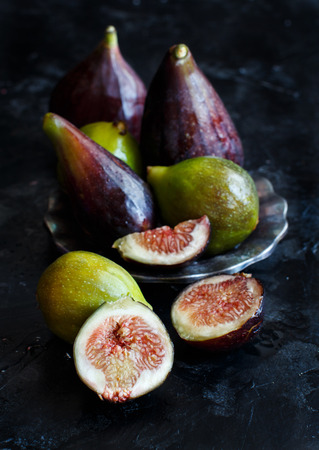Green and purple figs  on a dark  background