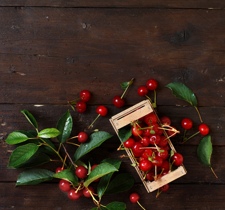 Fresh sour cherries in a box on a wooden table Archivio Fotografico