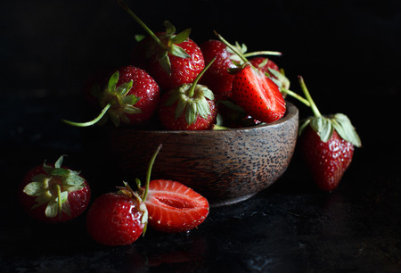 Strawberries in a bowl on a dark wooden table