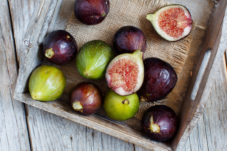 Green and purple figs  on wooden rustic background