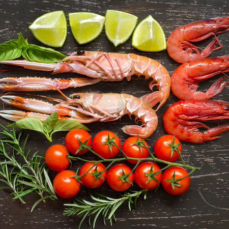 Raw langoustines and shrimps with vegetables on the dark wood Stock Photo