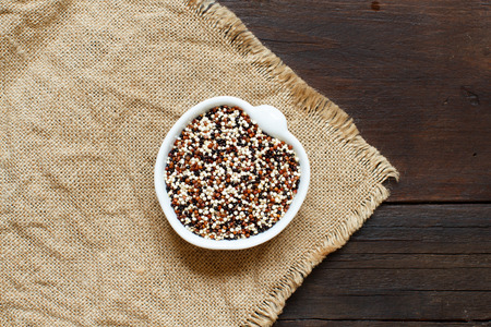 Pile of uncooked mixed red, white and black quinoa  in a bowl Archivio Fotografico
