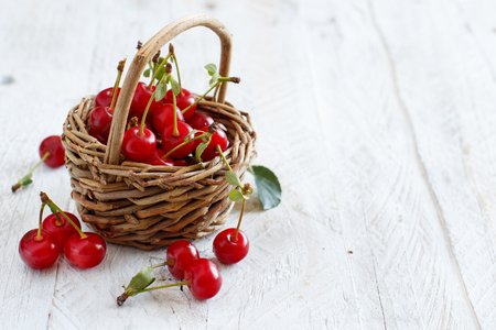 Fresh sour cherries in a basket on a wooden table Archivio Fotografico