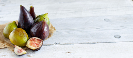 Green and purple figs  on a wooden table