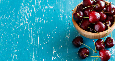 Red cherries in a bowl on a blue wooden background Archivio Fotografico