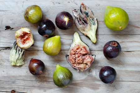 Green and purple figs  on a wooden table top view Archivio Fotografico