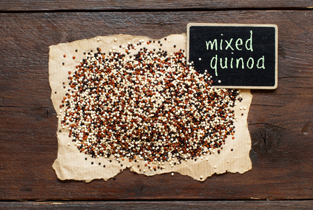 Pile of uncooked mixed quinoa with a small chalkboard top view Archivio Fotografico