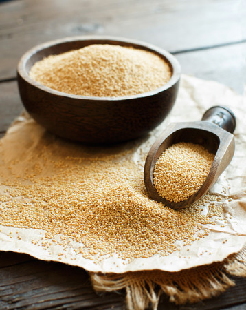 Raw Organic Amaranth grain in a bowl on wooden table Archivio Fotografico