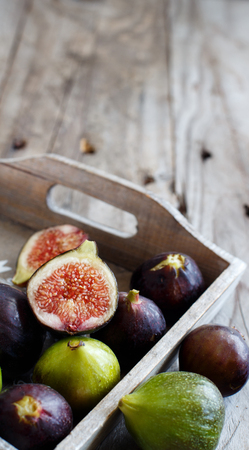 Green and purple figs in a box  on a wooden  background