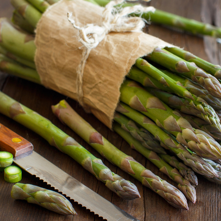 Fresh asparagus with knife on a wooden table Archivio Fotografico