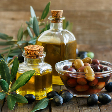 Olio d'oliva e olive su sfondo di legno rustico Archivio Fotografico