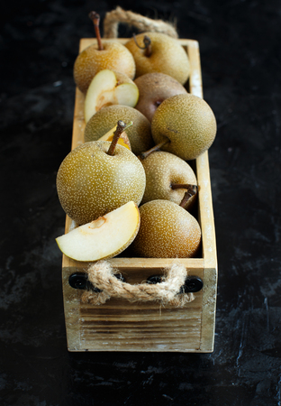 Nashi Pears (apple pears or asian pears) in a wood box on a dark background