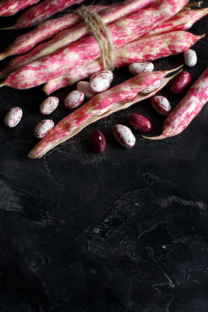 Pinto beans with pods on a wooden table close up  Archivio Fotografico