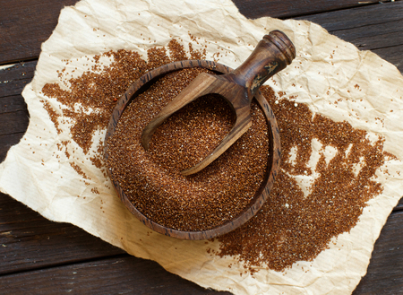 Pile of uncooked  teff grain in a bowl with a spoon close up Archivio Fotografico