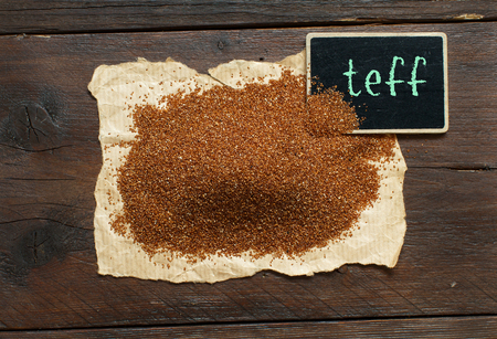 Pile of uncooked  teff grain with a small chalkboard