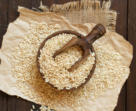 Pile of Brown rice  on wooden background top view Imagens