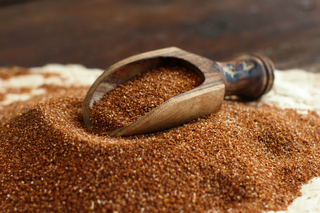 Pile of uncooked  teff grain with a spoon close up