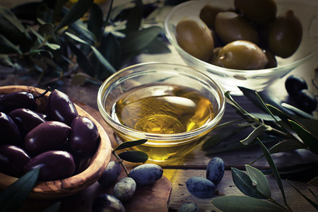 Olive oil and olives on rustic wood background retro styled