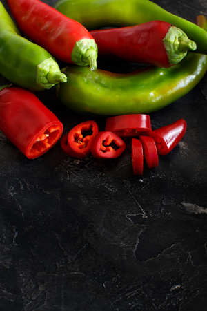Red and green sweet peppers on wooden background