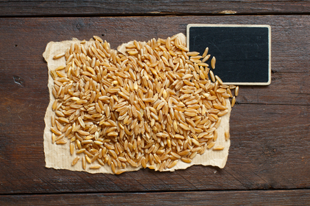 Pile of Kamut grain on wooden background with small chalkboard Archivio Fotografico