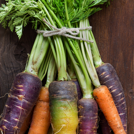 Fresh organic rainbow carrots with leaves on a wooden table