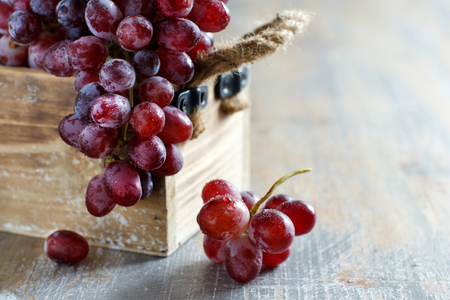Grapes in a wooden boxon an Old Wooden table Archivio Fotografico