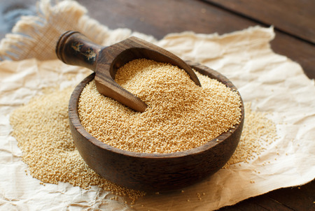 Raw Organic Amaranth grain in a bowl on wooden table Stock Photo