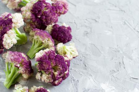 Fresh raw purple cauliflower on a grey  board close up
