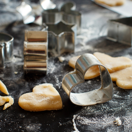 Close up of cookie cutters and dough on a dark table Archivio Fotografico