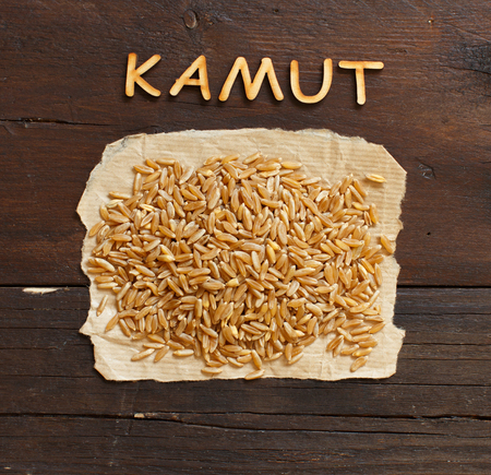 Pile of Kamut grain on wooden background top view Archivio Fotografico