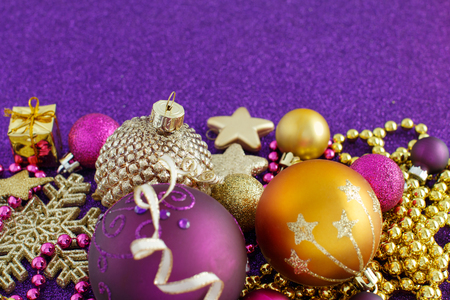 Golden and purple Christmas decorations and baubles close up