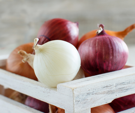 Raw onions in a box on a wooden table