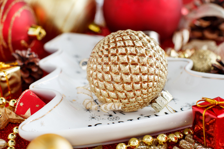 Red and golden festive christmas decorations with plate