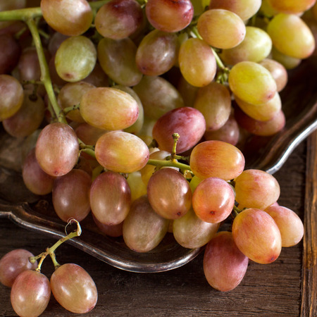 Grapes on silver tray on an Old Wooden Background Archivio Fotografico