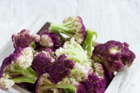 Fresh raw purple cauliflower on a wooden board close up Archivio Fotografico