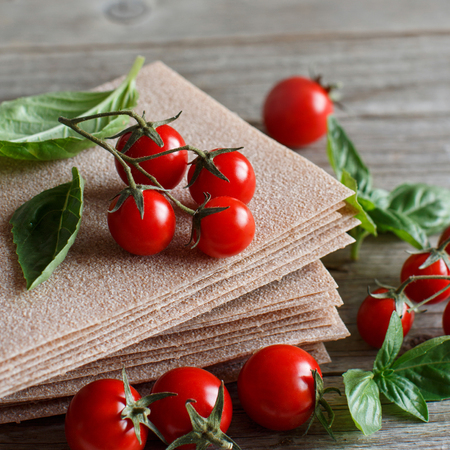 Raw lasagna sheets,basil and cherry tomatoes on a wooden table  Archivio Fotografico