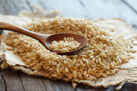 Pile of Brown rice with a wooden spoon close up
