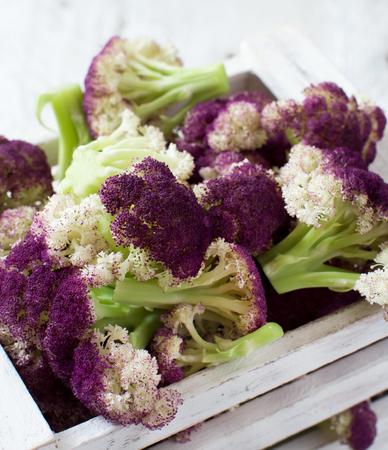 Fresh raw purple cauliflower in a wooden box close up Archivio Fotografico
