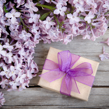 Gift box with purple bow and lilac on wood Archivio Fotografico