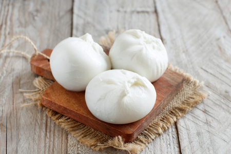Italian cheese burrata on a wooden table close up