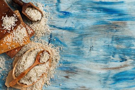 Keltisch grijs zeezout met een lepel op een blauwe houten tafel