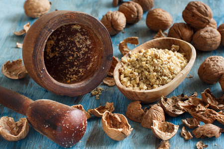 Fresh walnuts with mortar and pestle on a blue wooden table close up Stock Photo