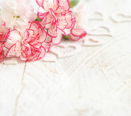 Spring background with flowers and hearts on a white wooden tabe Archivio Fotografico