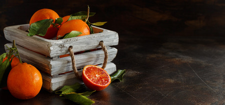 Fresh  oranges with leaves on an old table
